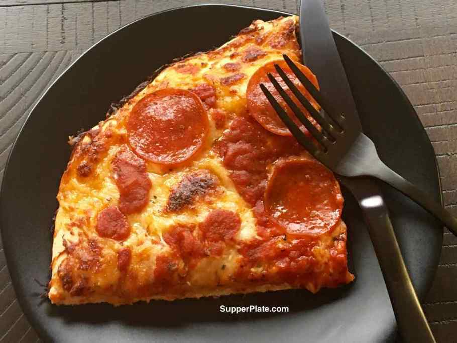 Pizza on a black plate with a black fork and knife