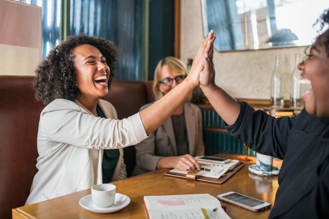 Diverse women high-fiving at a table