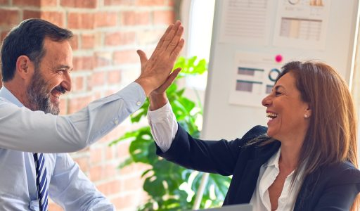 Man and woman high-five in an office