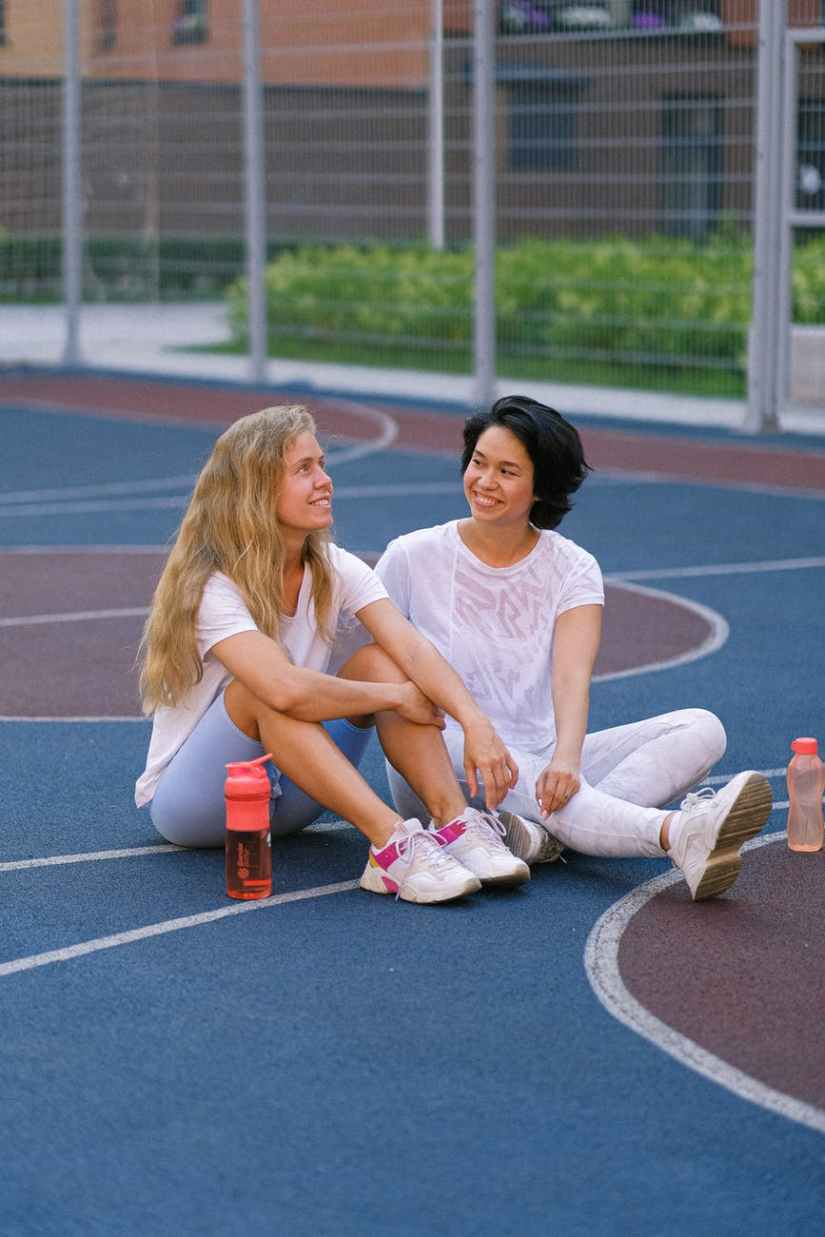 positive female friends sitting on sports ground after training