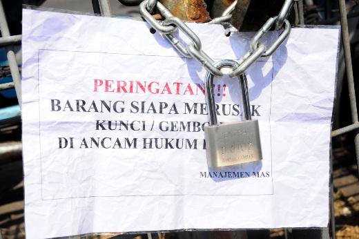 Kertas peringatan yang tertempel pada pagar yang terkunci dengan gembok memicu amarah sejumlah PKL Pagesangan yang biasanya mencari nafkah dengan berjualan di lahan kosong samping Masjid Agung Surabaya. (FOTO : hercox untuk surabayaupdate.com)