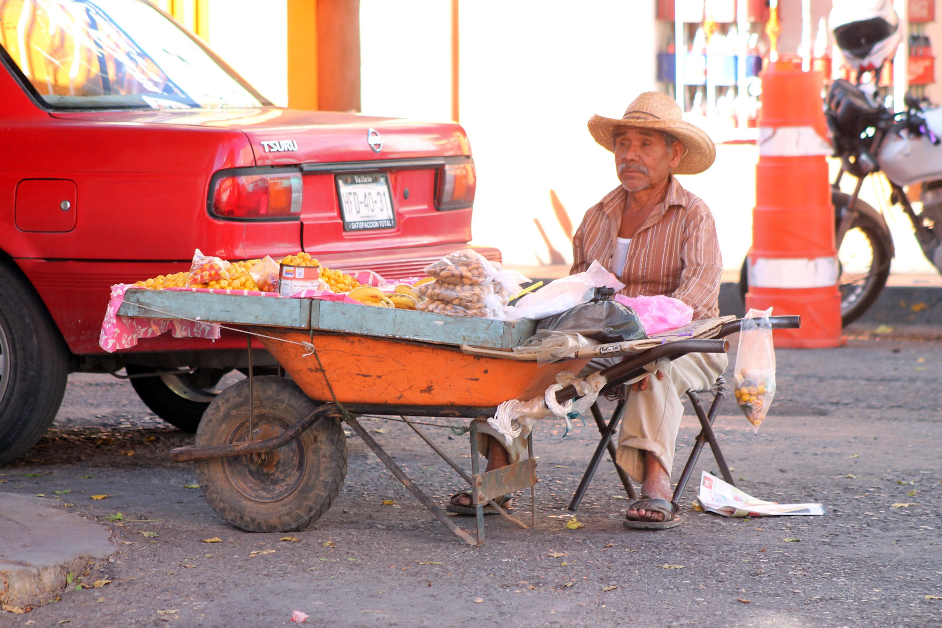 Ante la falta de oportunidades de empleo hay más vendedores ambulantes en el primer cuadro de la ciudad; en la imagen un señor de la tercera edad ofrece cacahuates y nanches sobre la calle Juan Ruíz de Alarcón en el centro de Chilpancingo. Foto: Jesús Eduardo Guerrero