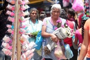 Una adulta mayor camina con un ramo de flores y bolsas de comida entre puestos de regalos en el mercado Baltazar R. Leyva Mancilla, el día previo a la celebración del Día de las Madres. Foto: Jessica Torres Barrera