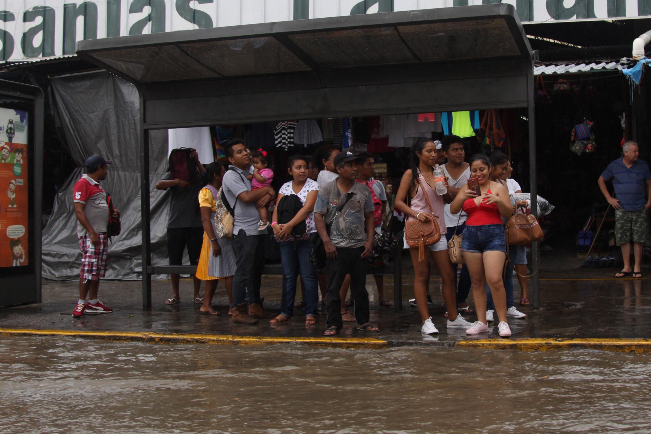Acapulco,Gro/16enero2019/ Varias personas esperan el transporte público en la parada de camiones , mientras se cubren  de la lluvia que cayó la tarde de ayer  en Acapulco. Foto: Jesús Trigo