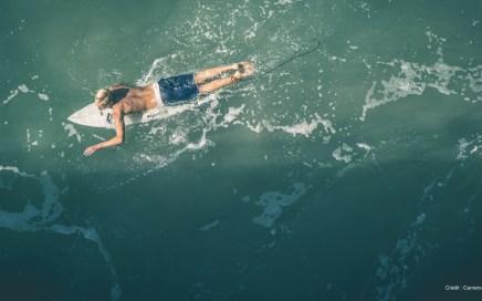 Surfeur sur sa planche - Éviter les irritations lors de la pratique du surf