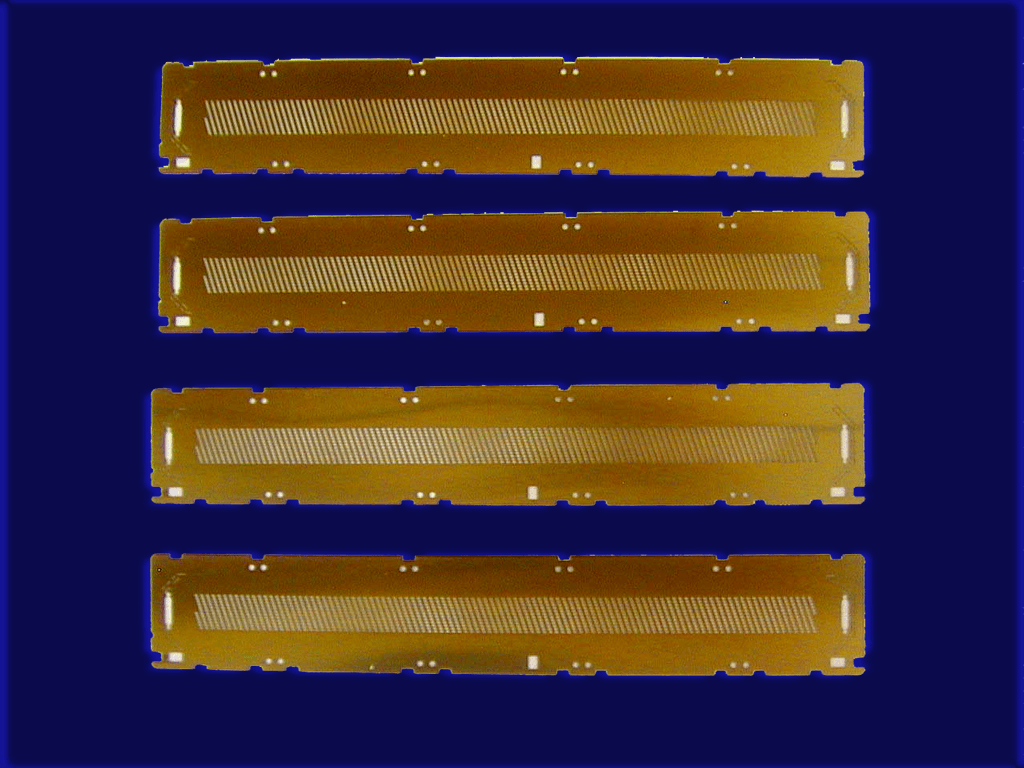 Photo of four tin-coated thin metal parts surface treated by Surface Engineering Technologies LLC