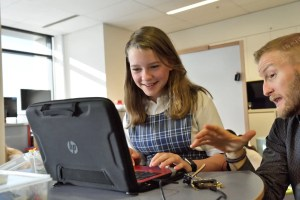 Girl smiling on a computer with a teacher motion an instruction with hand.