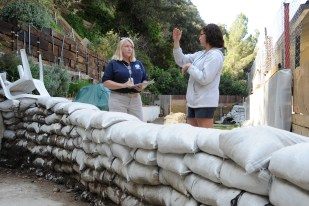 La Canada, CA - Homeowner Olivia Brown explains the mitigation best practice procedure of sandbagging to FEMA Disaster Assistance Employee Barbra Ellis. The area suffered severe floodind, debris flows and landslides as a result of winter storms, but this savy homeowner avoided flooding to their home due to proper planning. Adam DuBrowa/FEMA