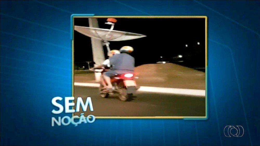 Homens são flagrados carregando antena parabólica em moto