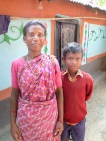 Une femme santale et son fils devant leur maison