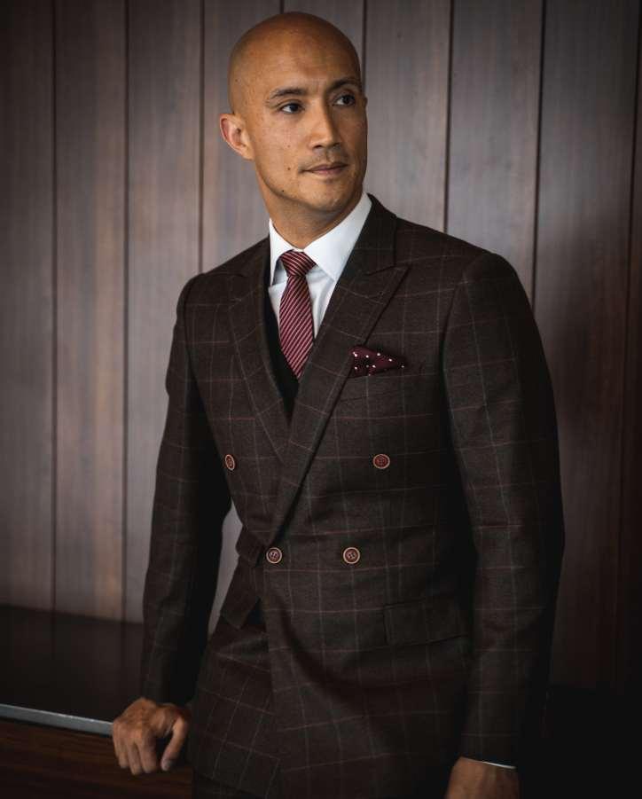 Homme asiatique portant un costume marron à motifs, une cravate à rayures rouges et un mouchoir à pois.