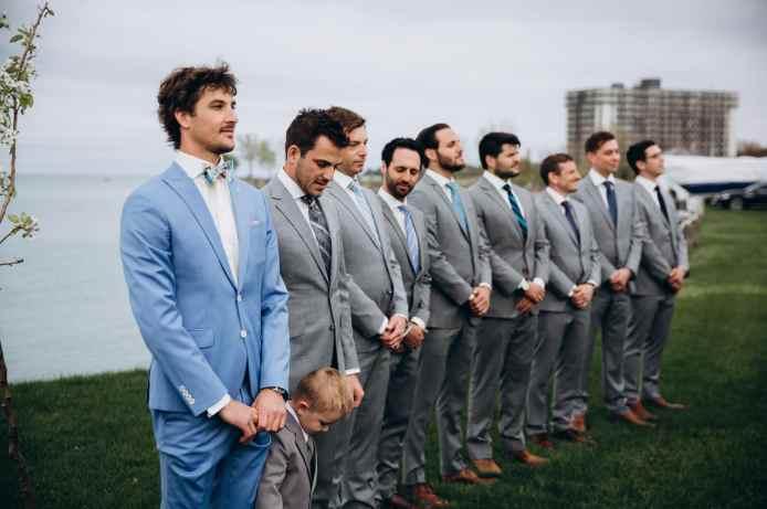 Groom in light blue suit accompanied by groomsmen in light gray suits