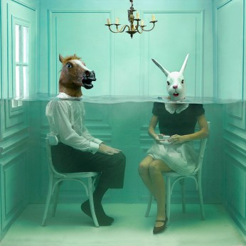 Man and woman wearing animal masks sitting in a small room filled with water