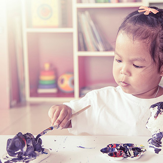 A young girl painting a sculpture