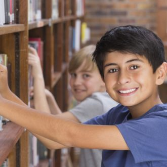 Kids standing in the library near a bookshelf