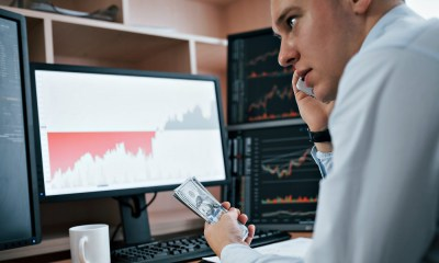 Feature   Man working online in the office with multiple computer screens in index charts   Ways To Prepare For Economic Collapse   Things You Should Do