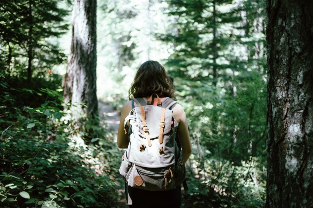 a girl carrying a backpack in the middle of the forest | Bug Out Bags For Women | best bug out backpack for women