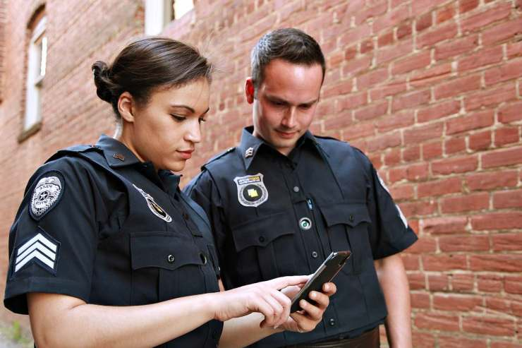 Two police officer looking in mobile phone | Home Security And Crime Prevention Secrets