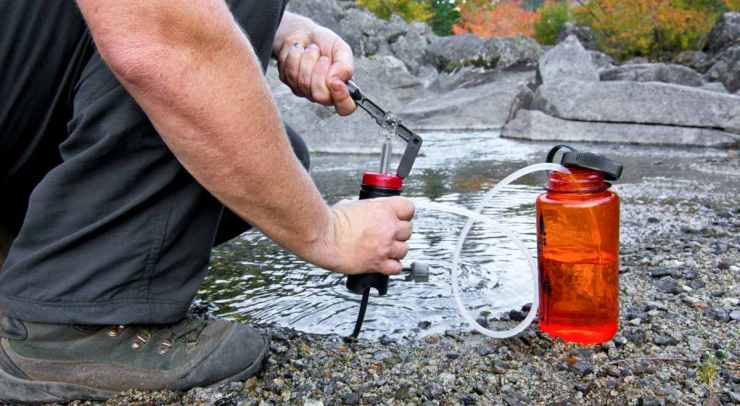 A person uses a lightweight compact water filter to pump safe drinking water | How To Collect And Store Water For Survival And Off Grid Living