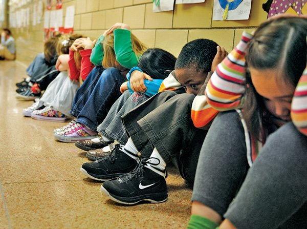 Students undergo a tornado drill at school. (Image via)