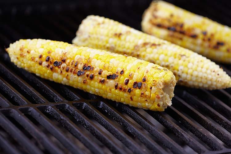 Three cobs of corn on a grill.