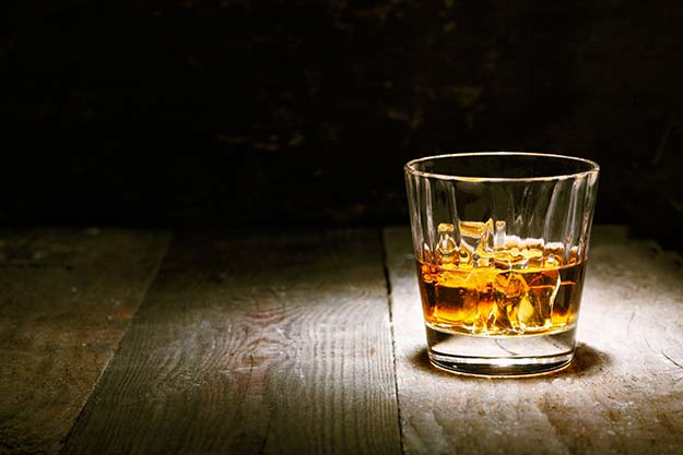 A tumbler of whiskey on the rocks sitting on a bar.