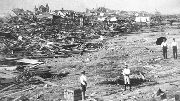 A black and white photo of men standing among the wreckage left by the Galveston hurricane of 1900.