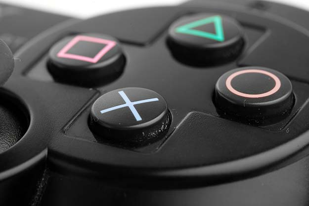 Close-up of the four buttons on a black PlayStation remote.