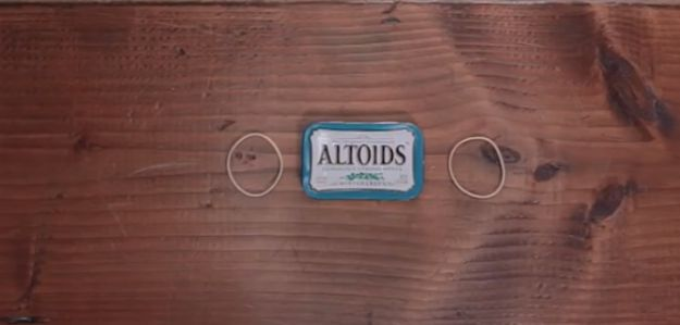 Step 1: Start with an  empty Altoids tin and two rubber bands to hold the tin shut | How To Build The Perfect Pocket-Sized Survival Kit