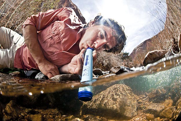 A man drinking from a river using a LifeStraw water filter.