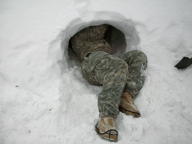 snow-cave-with-man-in-camo-half-inside Snow Shelter: Learn How to Build a Snow Cave For Winter Survival
