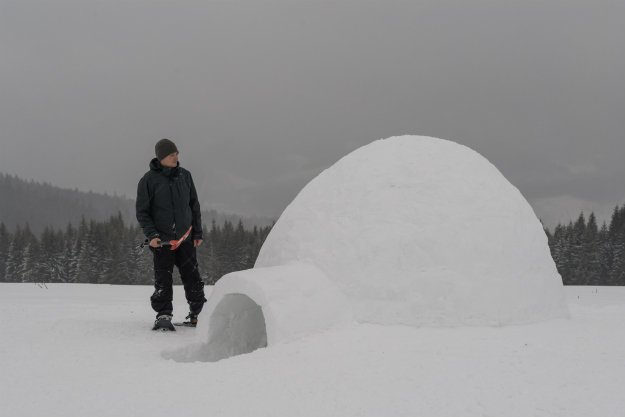snow-sheter-with-man-standing-outside Snow Shelter: Learn How to Build a Snow Cave For Winter Survival