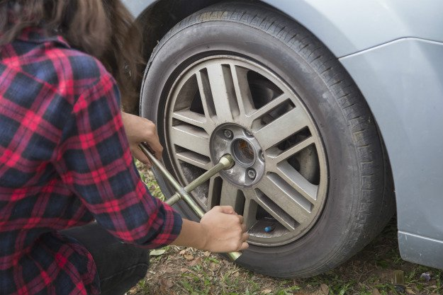 girl-changing-tire Survival Emergency Car Kit | The DIY Kit That Could Save Your Life