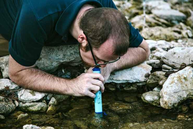 a man using a water filter | Best Survival Gear