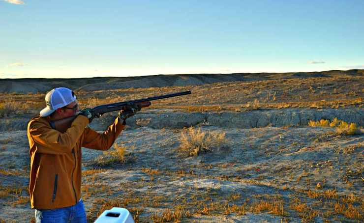 A man wearing yellow jacket firing a shotgun | These Hunting Shotguns Are The Best Bang For Your Buck