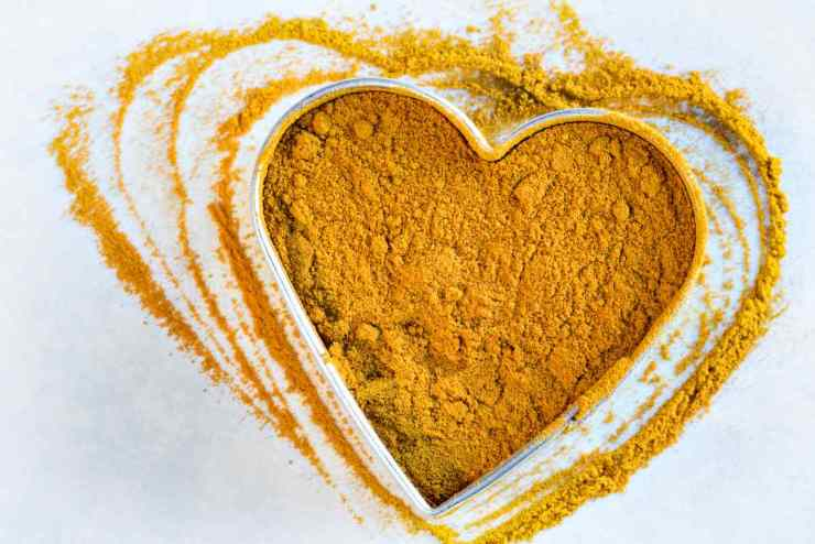 Ground turmeric in a heart shape | Turmeric Benefits: Improving Your Health And Natural Healing At Home