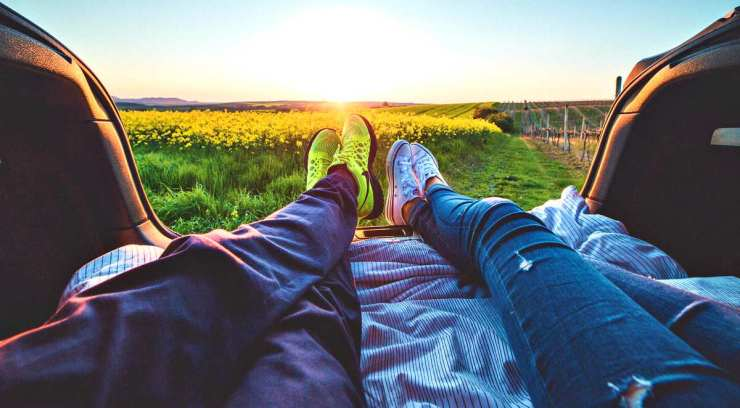 Two people sitting with view of yellow flowers during daytime | Minimalist Footwear...An Ultralight Essential? [Gear Review]