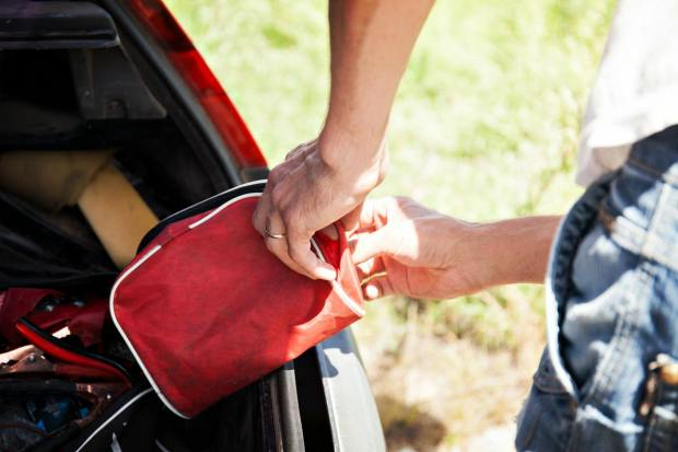 The man is lying first-aid kit in the trunk of the car | Travel Safety Tips You Shouldn't Ignore