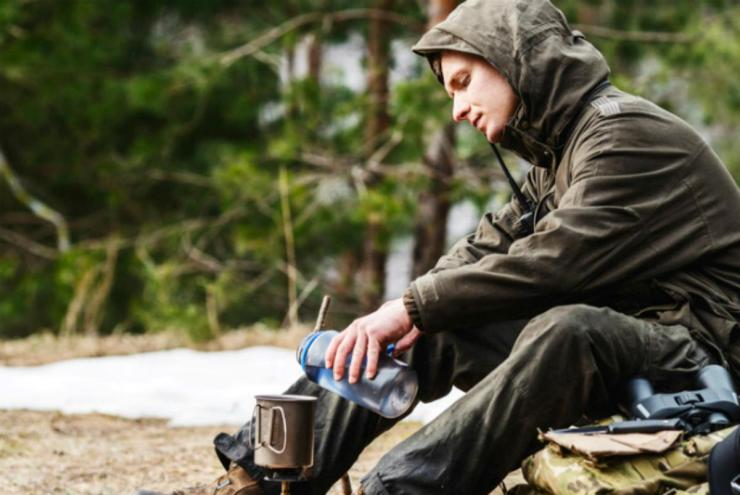 Hunter cooking food with a portable gas burner | Coffee Can Survival Kit: Don't Travel Without It