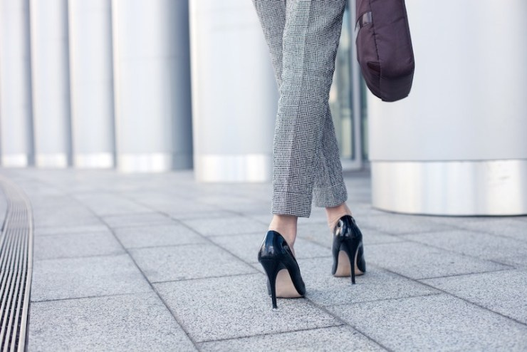 Close up of female legs of worker standing near her office. The woman is wearing formalwear and shoes on high heels. She is holding a handbag. Copy space in left side | lady's technique