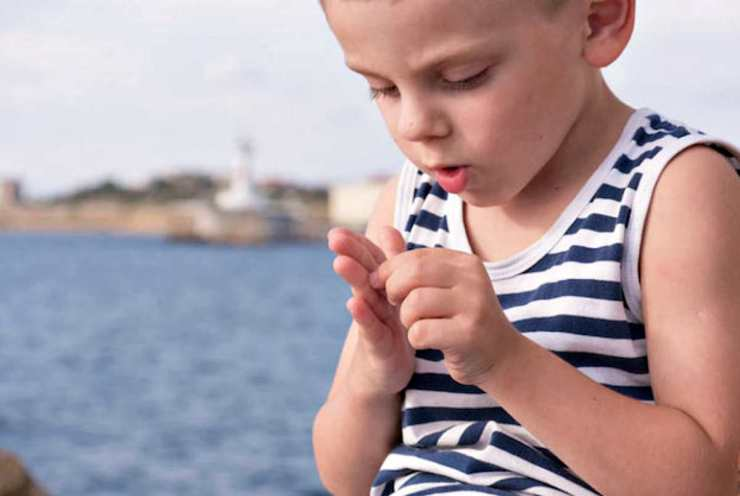 Boy looking to his hand | Lavender Oil Survival Uses