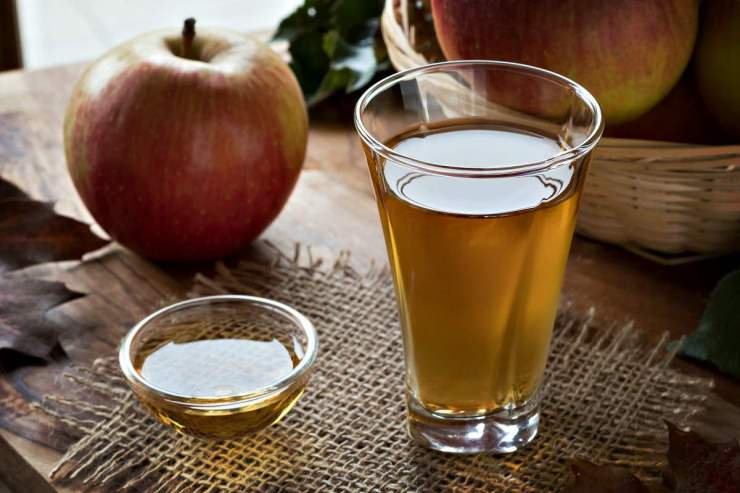 Apple cider vinegar in a glass, with apples in the background | Chicken And Duck Keeping | Top Natural Remedies For Your Sick Flock