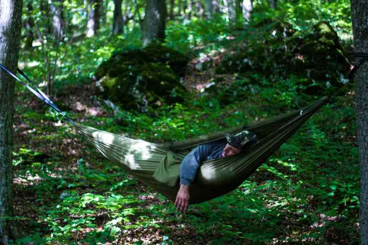 Man sleeping in green havoc | How To Build An Overnight Bushcraft Camp