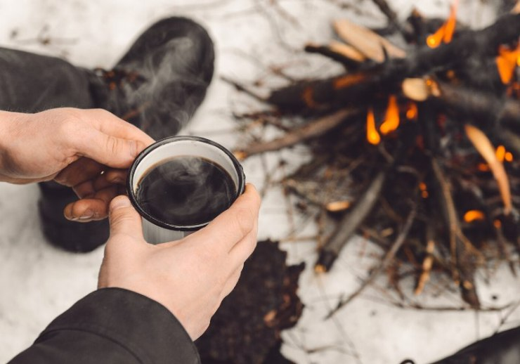 male hands hold mug coffee near | how to start a fire in the woods