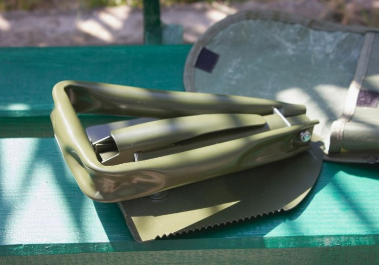 military spade folded on green bench | extreme cold weather work gear