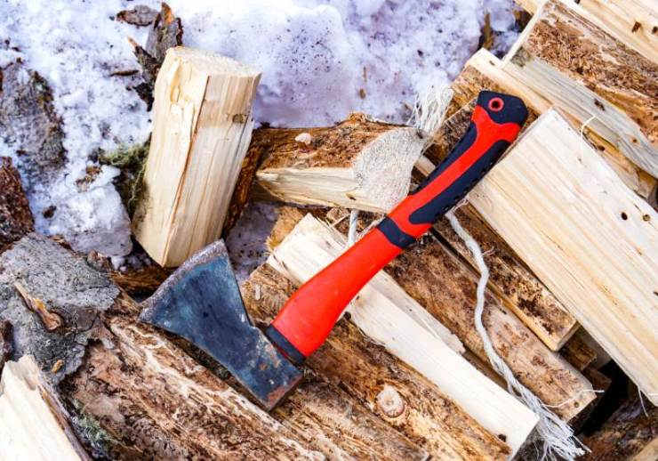 red tourist hatchet on chopped wood   extreme winter survival