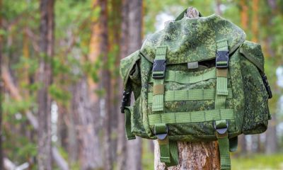 small backpack hanging on trunk tree | How To Turn Your Bug Out Bag Into A Minimalist Backpack | featured