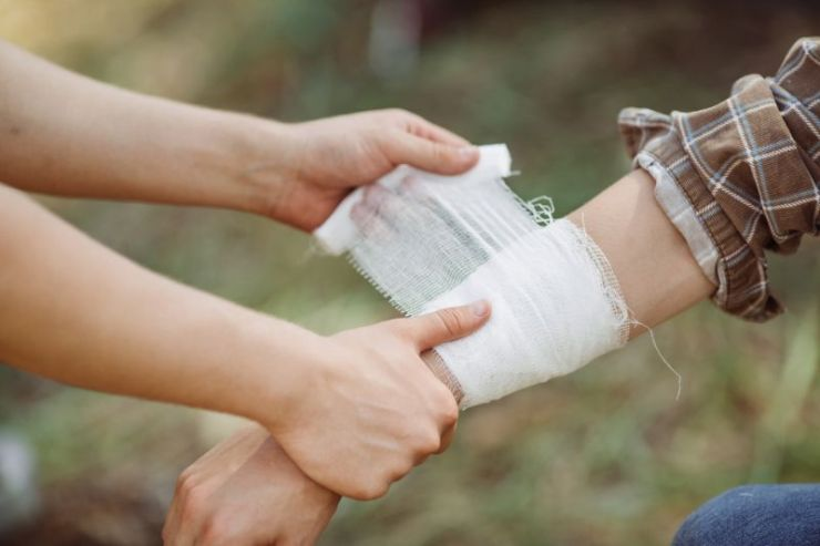 person-wrapping-his-friends-injured-arm | first aid