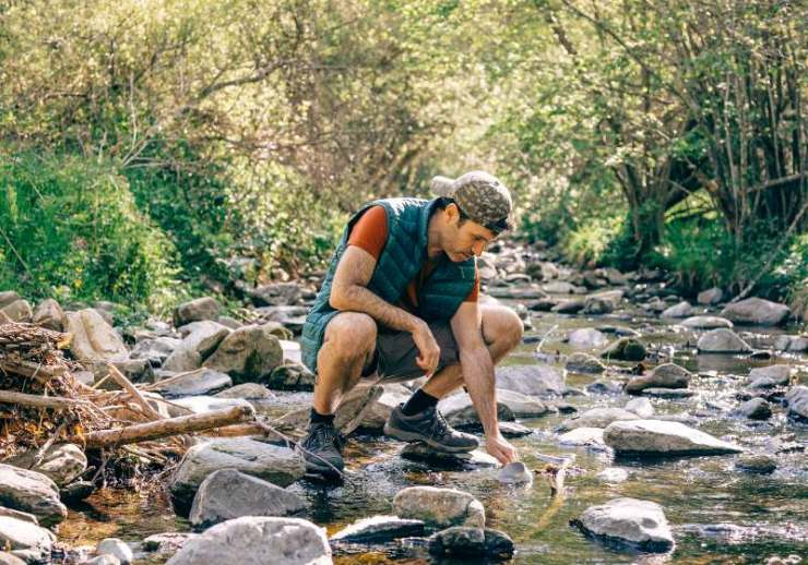 hiker collecting water creek middle forest | community water systems