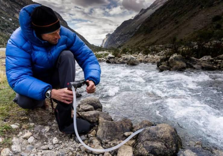 man blue down jacket filtering water | potable water treatment